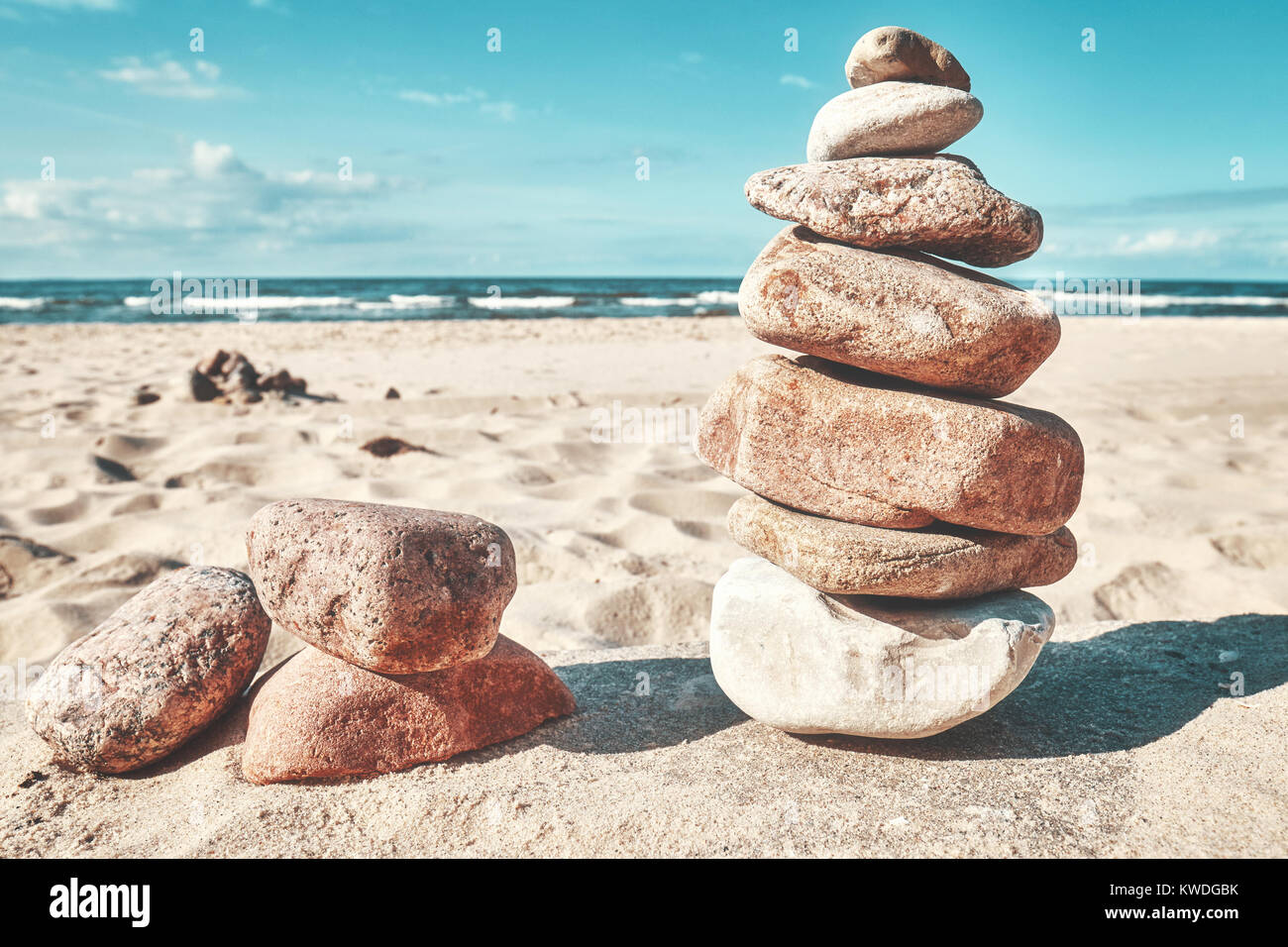 Retro toned picture of a stone stack on a beach, zen like natural background. - Stock Image