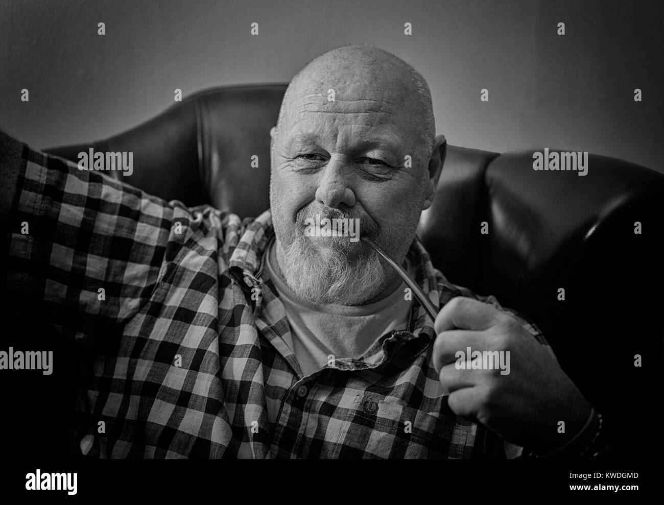 A mature male sitting in a wing back chair holding a pipe, in a reflective mood. - Stock Image