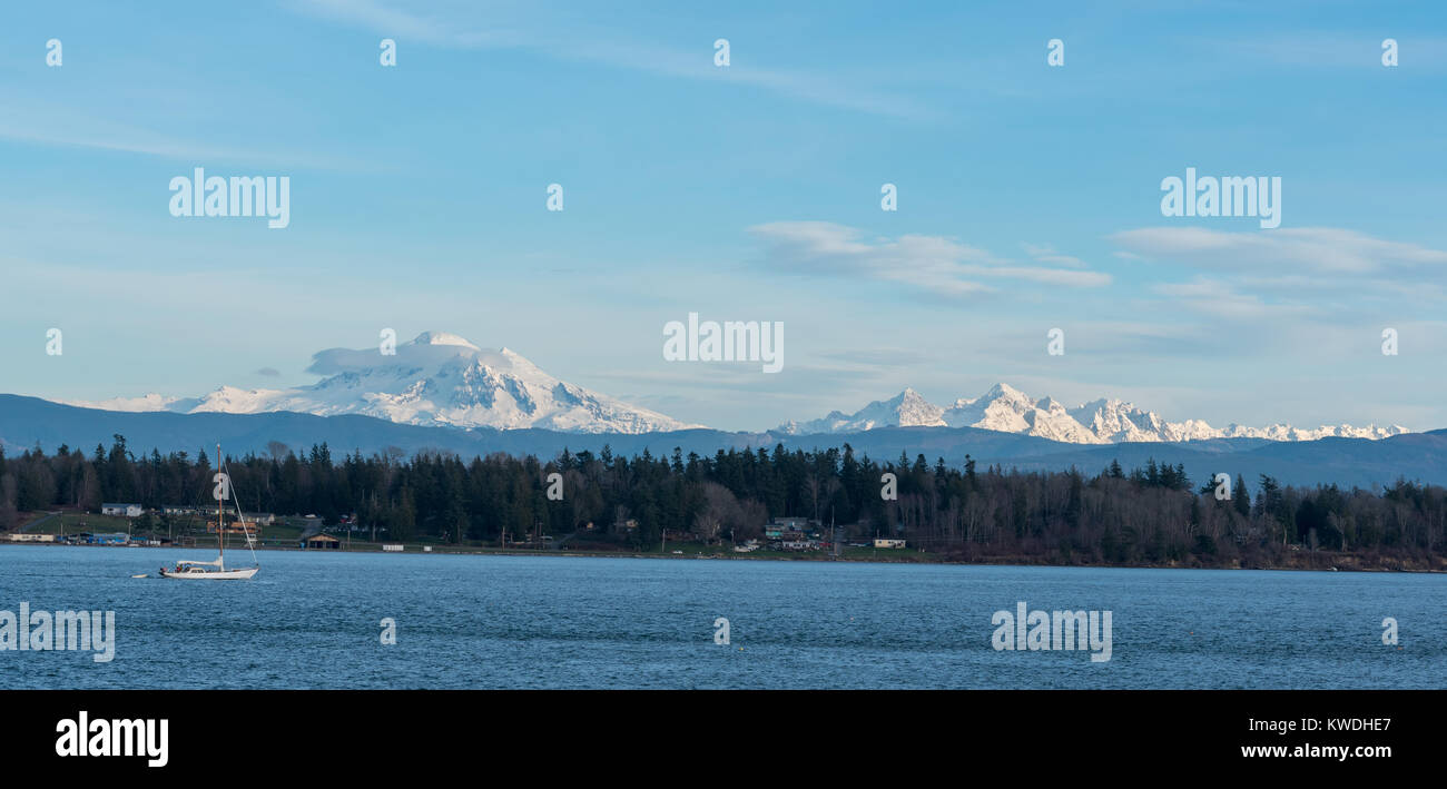 Sailboat motoring in Hale Passage, Washington.  Mt. Baker and The Sisters rise in the background. - Stock Image