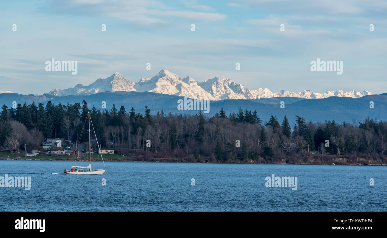 Sailboat motoring in Hale Passage, Washington.  The Sisters, peaks in the Cascade Range, rise in the background. - Stock Image