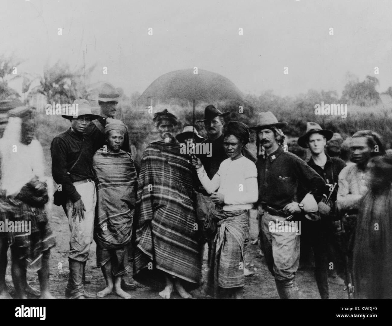 Captain John Pershing standing behind the Rajamunda of Marahai and his slave, holding an umbrella over the Rajamunda. - Stock Image