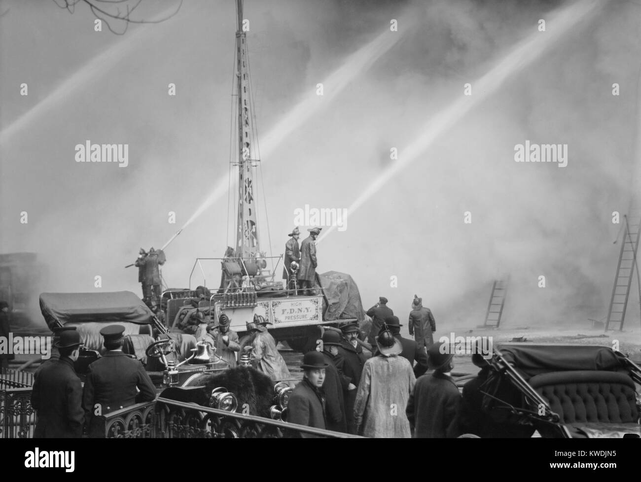 Firemen spraying three streams of high pressure water on a fire on 14th St., NYC, Dec. 1909 (BSLOC_2017_17_102) - Stock Image