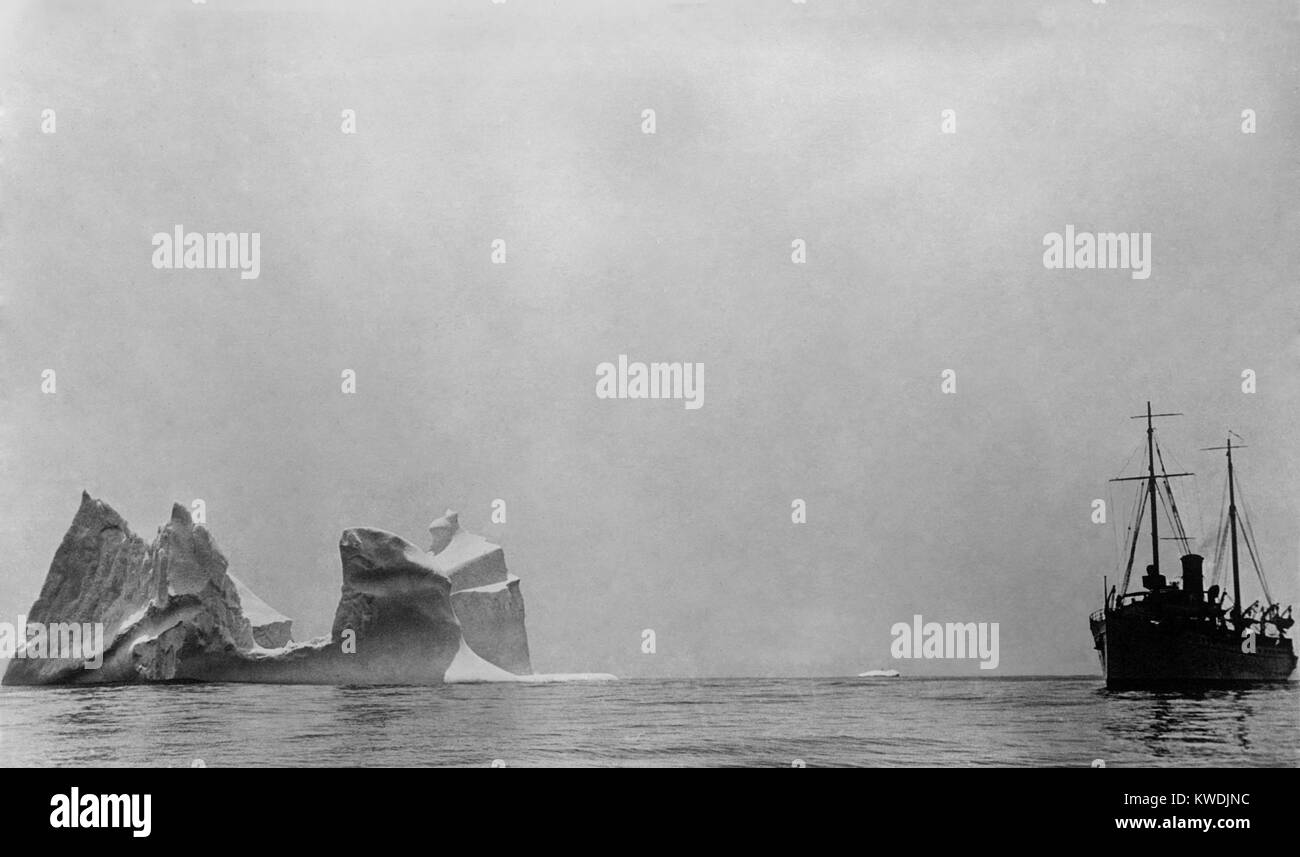 Ship passing an iceberg larger than the vessel. 1910-17, probably in the North Atlantic Ocean (BSLOC_2017_17_107) - Stock Image