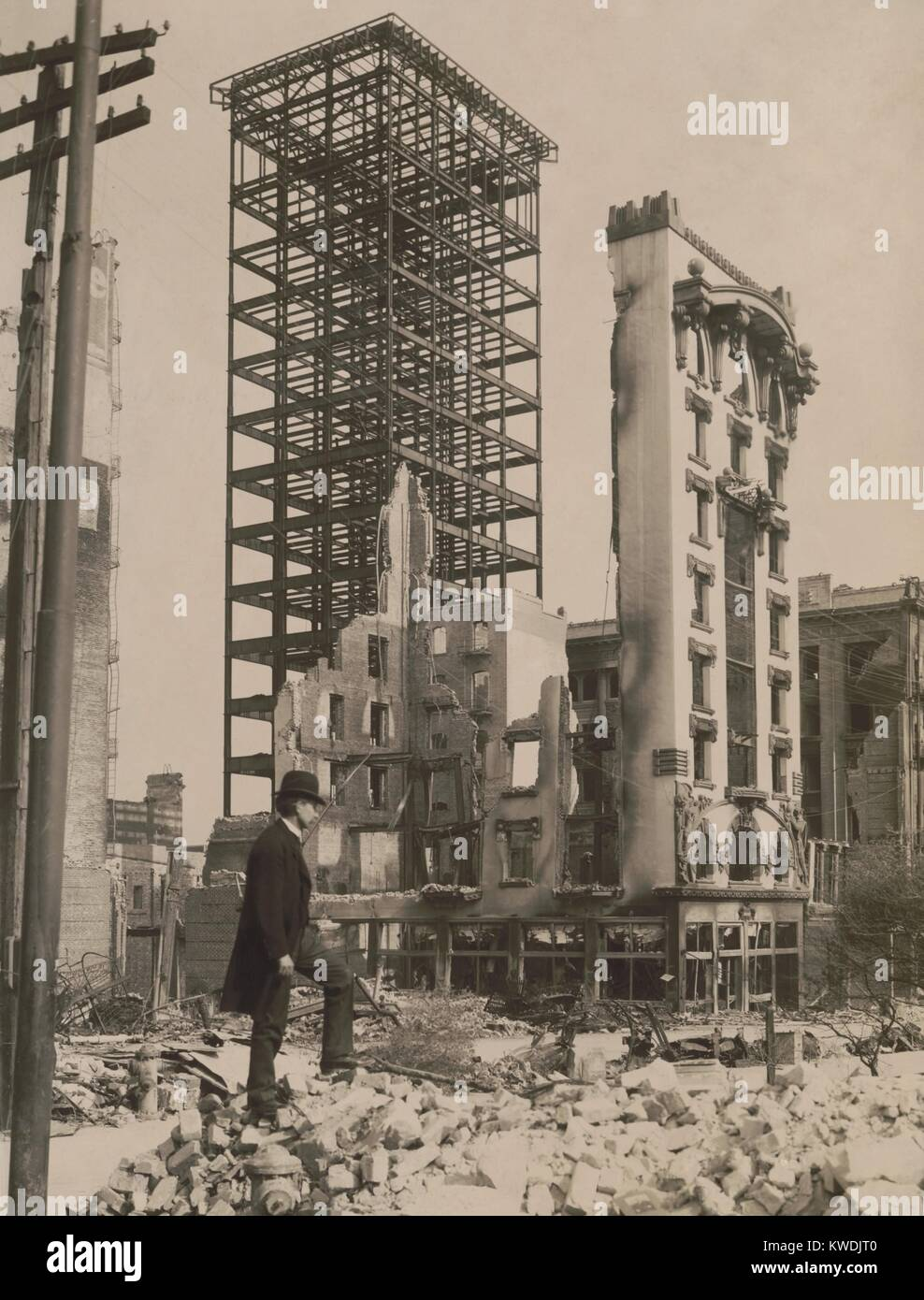 After the April 18, 1906 San Francisco earthquake, a man stands among rubble. In the background, an unfinished steel - Stock Image