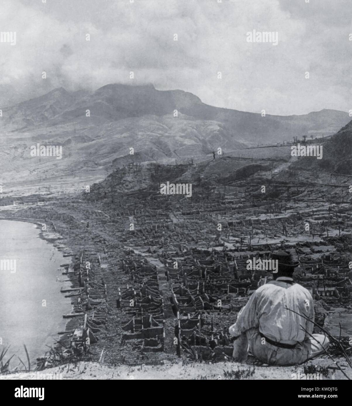 Man on Orange Hill looks over the dead city of St. Pierre, and up to steaming volcano, Mont Pelee. A pyroclastic Stock Photo