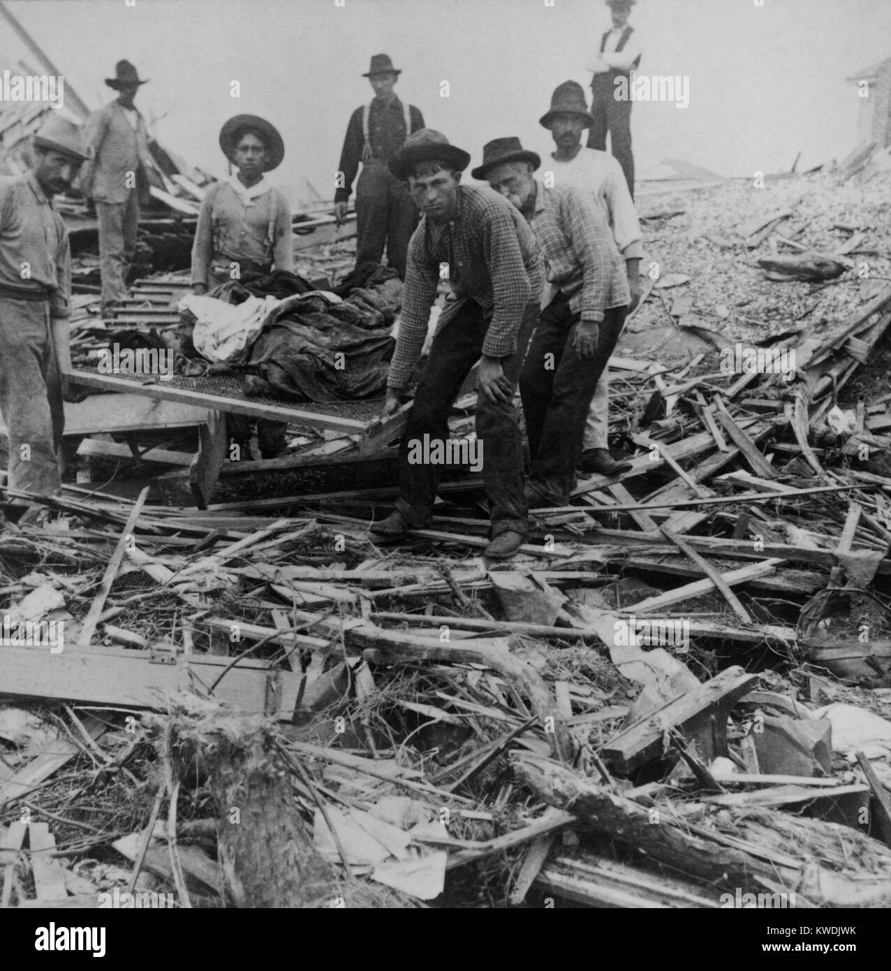 Men carrying bodies on stretcher, surrounded by wreckage of the hurricane in Galveston, Texas, Sept. 1900. The disaster - Stock Image