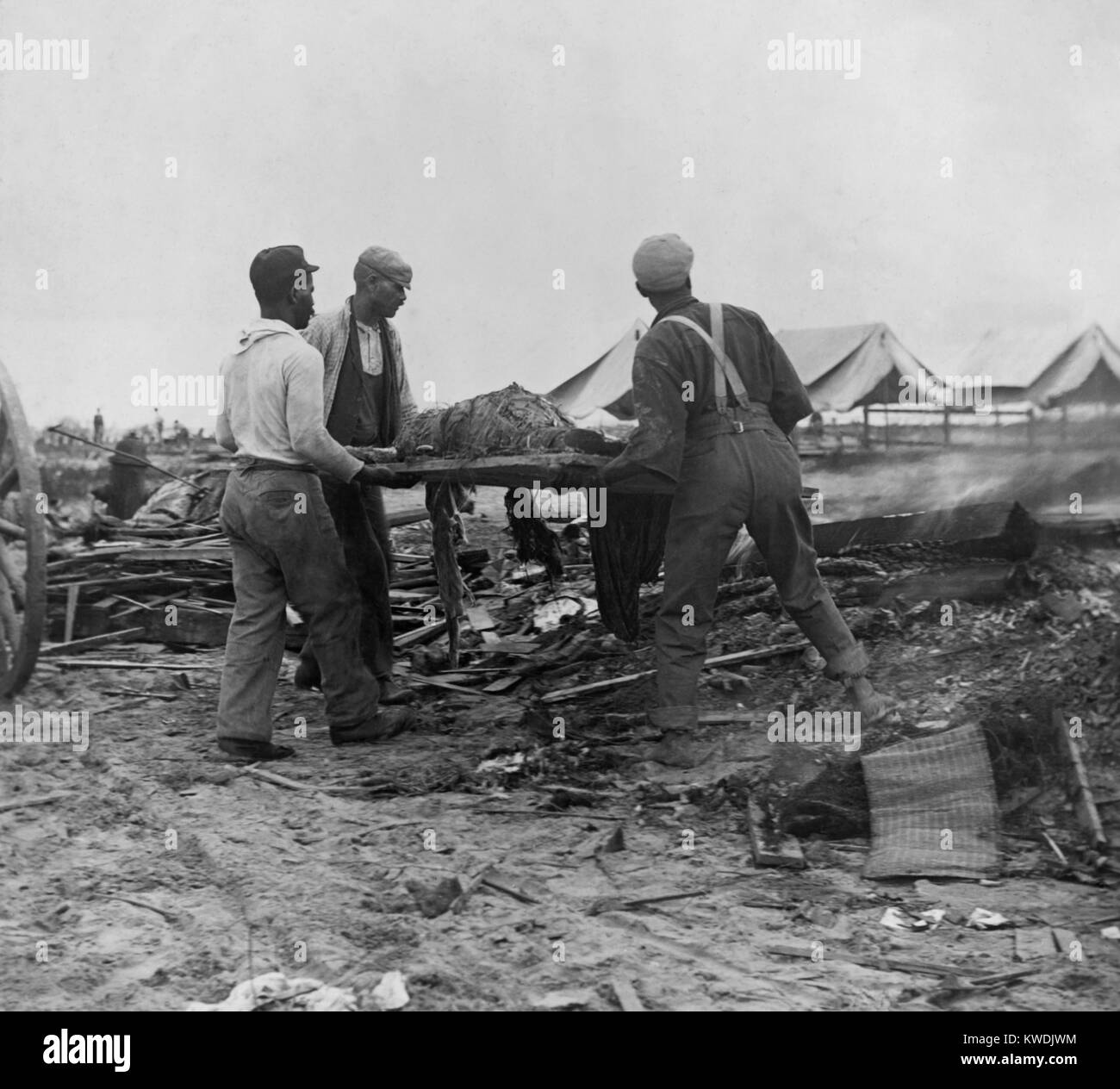 African American men carrying a body on stretcher to a fire (at right) to be cremated. Initial burials at sea caused - Stock Image
