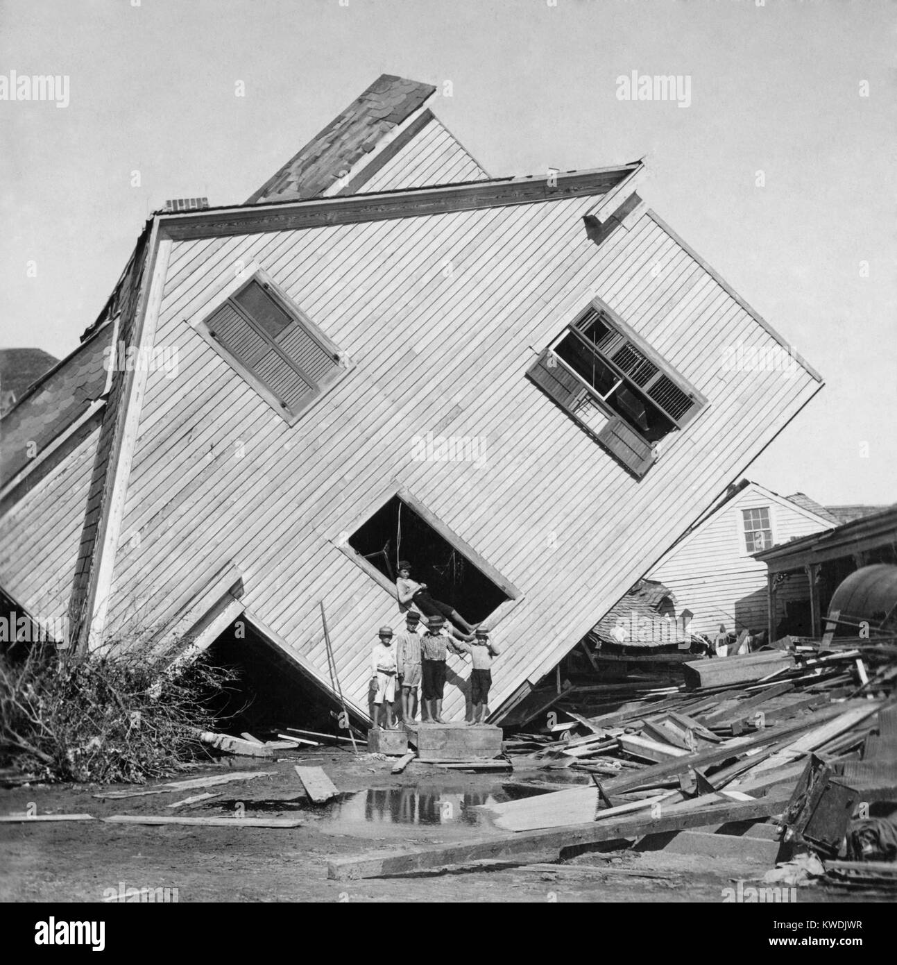 A house tipped on side after the 15 foot storm surge of the Galveston Hurricane of Sept. 1900. Five boys pose in - Stock Image