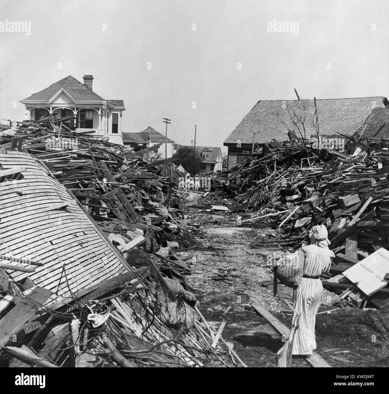 A woman walks through a passageway opened in the debris, on 19th Street, Galveston, Texas. In the distance stand - Stock Image