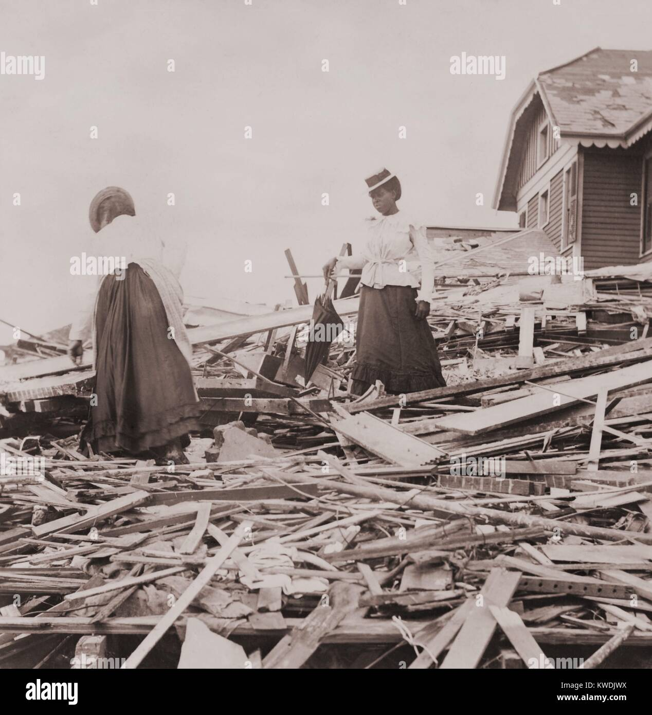 Two African American women on rubble trying to find where their Galveston home stood. 30,000 people were left homeless - Stock Image