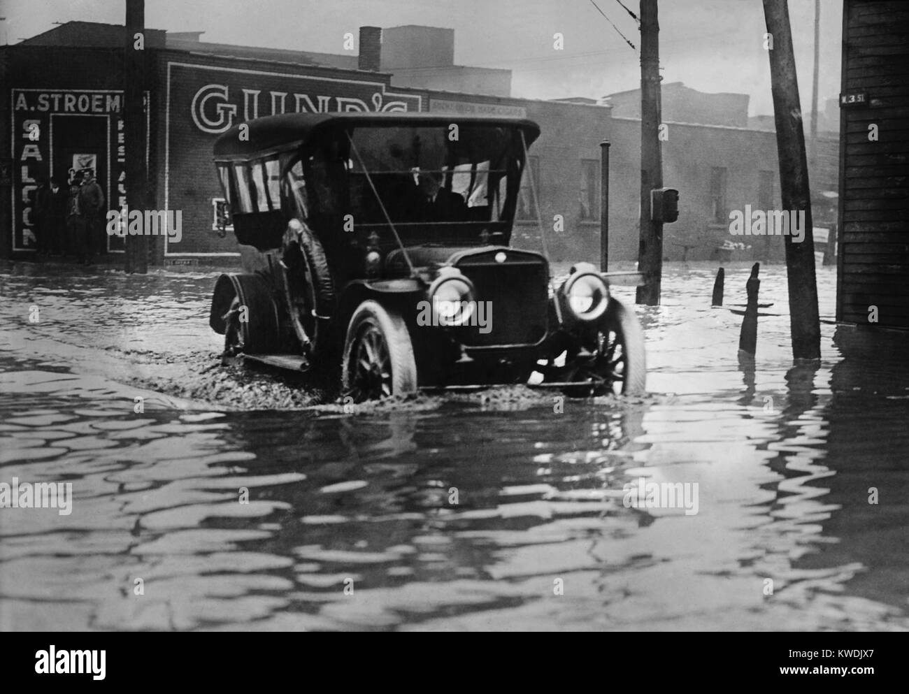 An automobile drives through axel high water on a flooded Cleveland street, probably in 1913. The early cars were - Stock Image