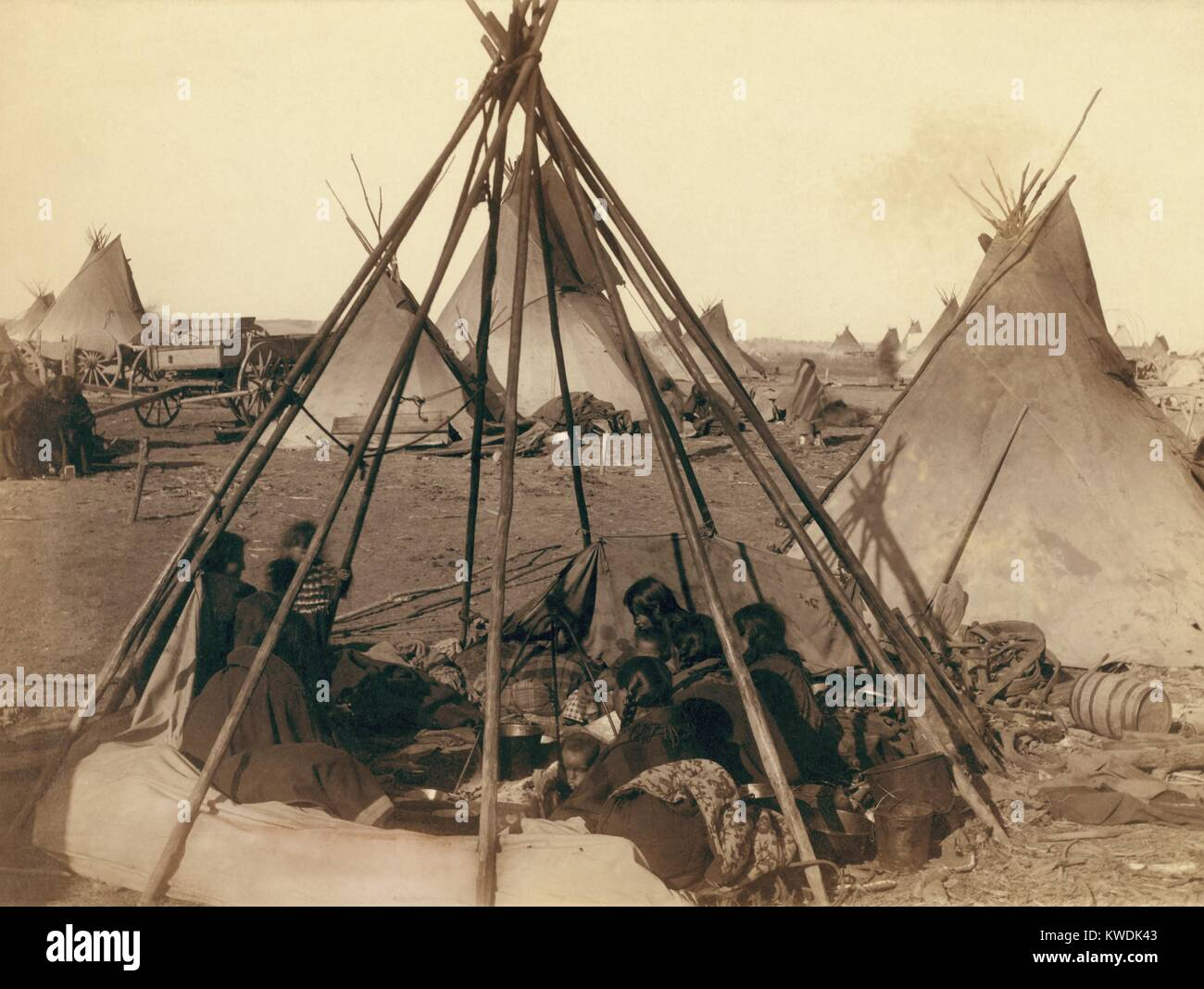 Oglala Sioux women and children inside an uncovered tipi frame near Pine Ridge Agency, Jan. 1891. Beyond are other Stock Photo