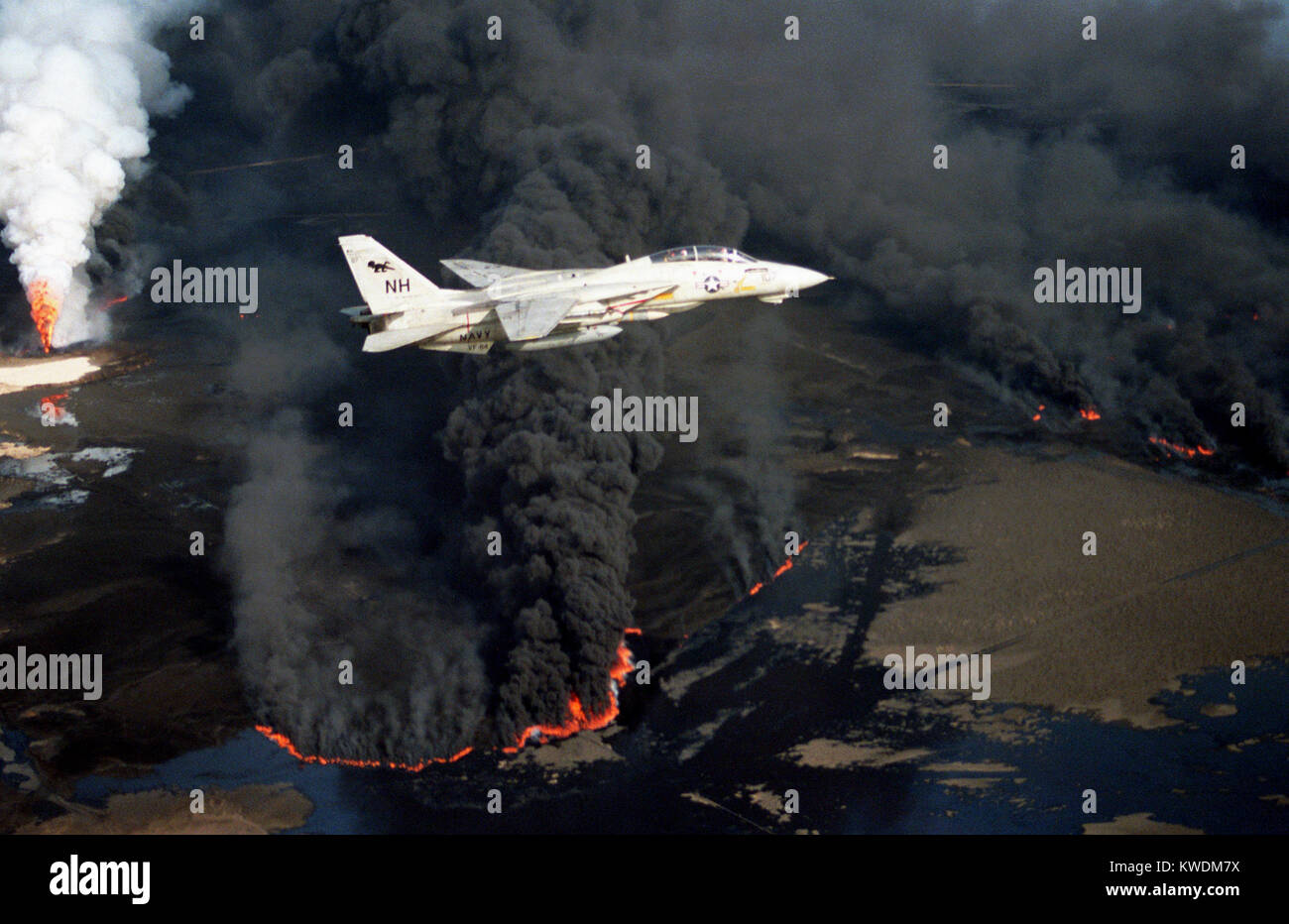 1991 Kuwaiti oil fires, U.S. Navy Grumman F-14A Tomcat flies over an oil well set ablaze by Iraqi troops during - Stock Image