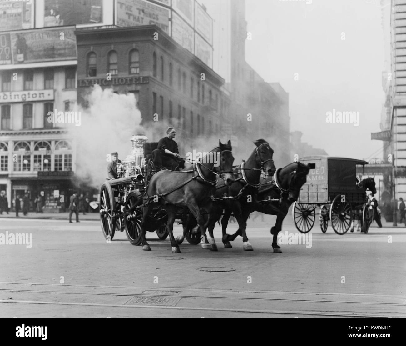 Horse drawn fire engine speeds on West 43rd Street and Broadway, NYC, 1910-15. The steam is from the engines boiler - Stock Image