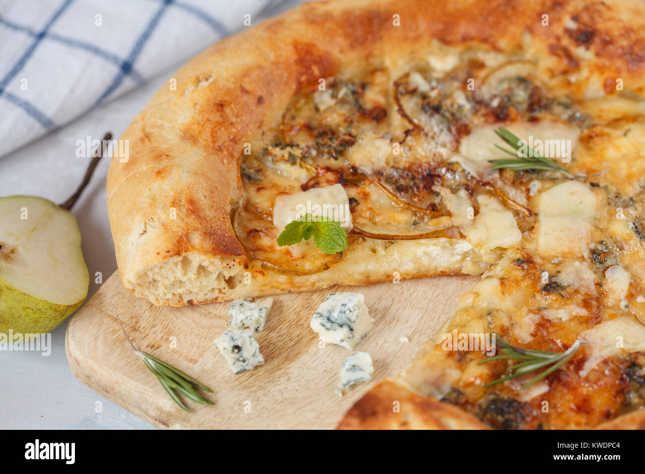 Hot delicous pizza with pear and blue cheese on wooden board. Vegetarian healthy food concept, traditional Italian - Stock Image