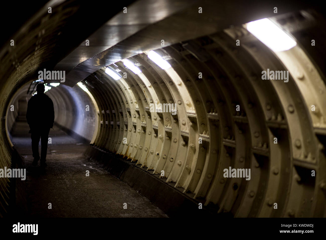 A shadowy figue walks in the Greenwich Foot Tunnel, Greenwich, London - Stock Image