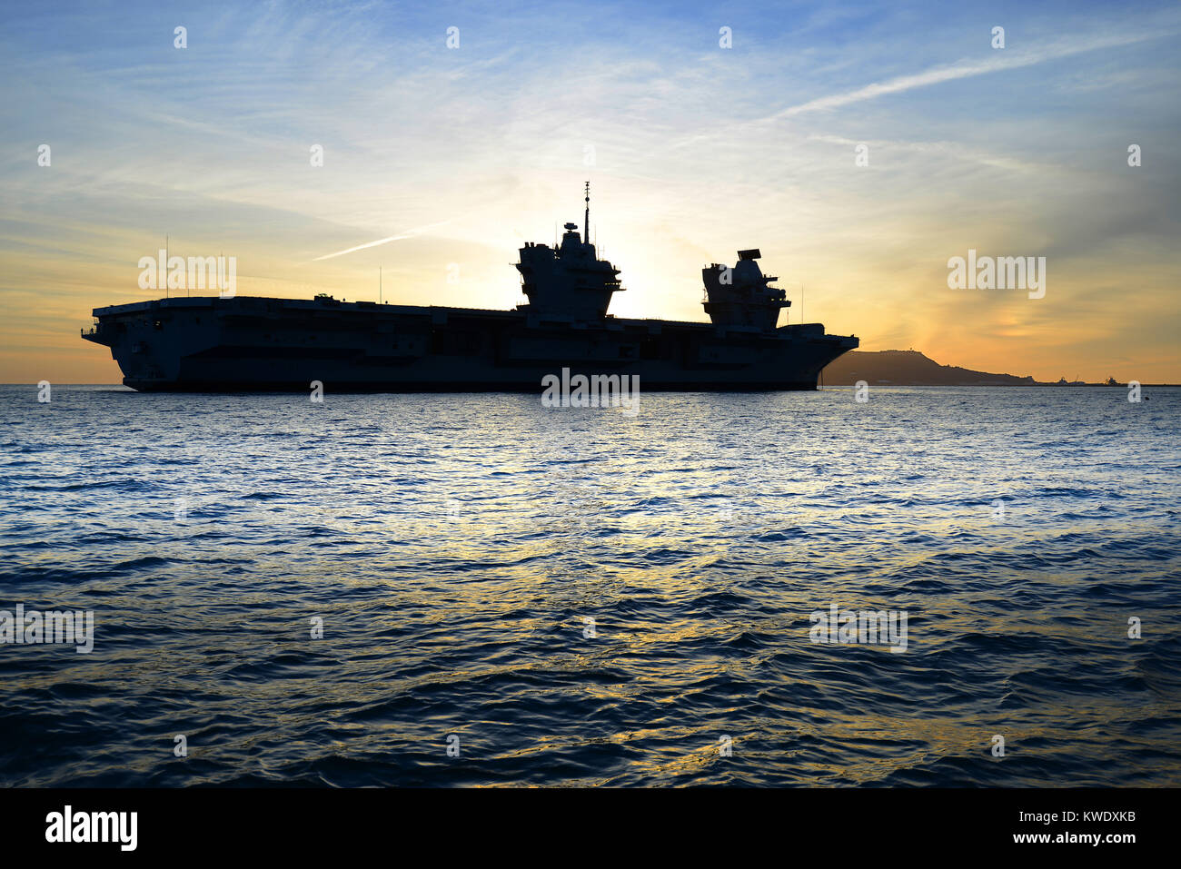 The Royal Navy aircraft carrier HMS Queen Elizabeth arrives at sunset at Portland, Dorset, on the Jurassic Coast - Stock Image
