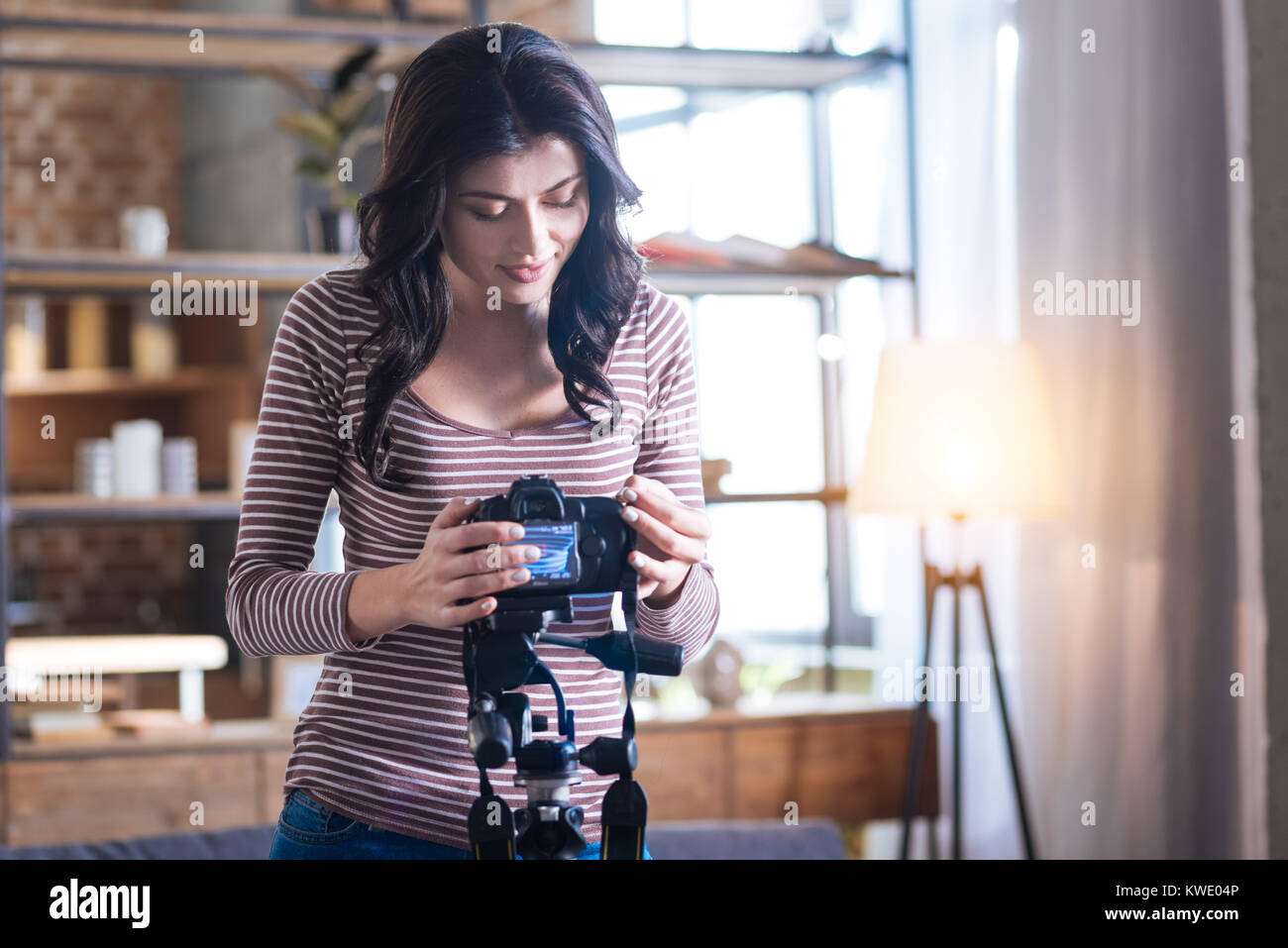 Pleasant brunette woman standing near the photo camera - Stock Image