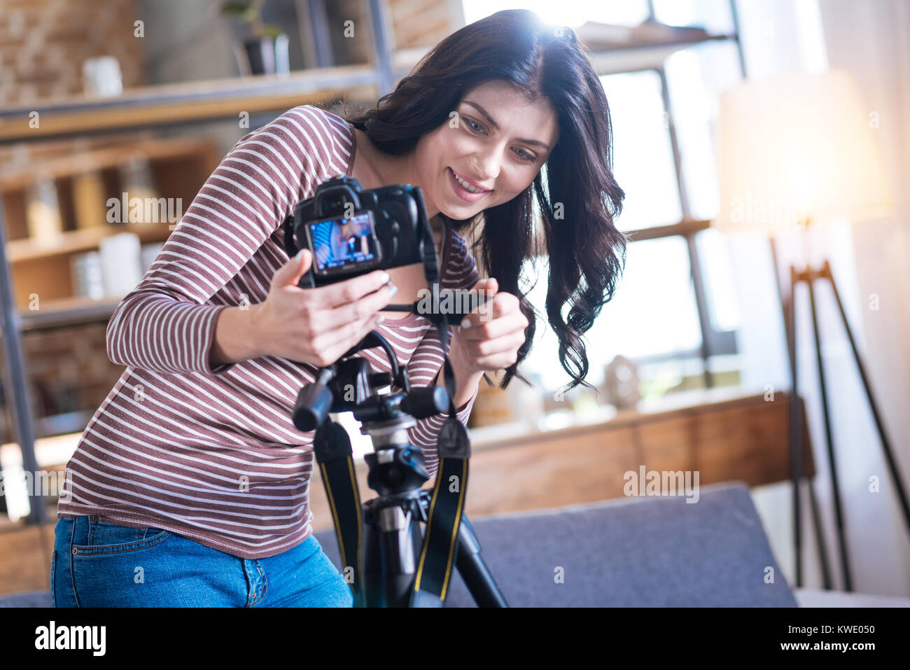 Positive nice woman setting up the camera - Stock Image
