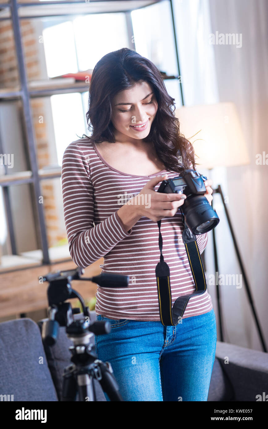 Cheerful nice woman looking at the photos - Stock Image