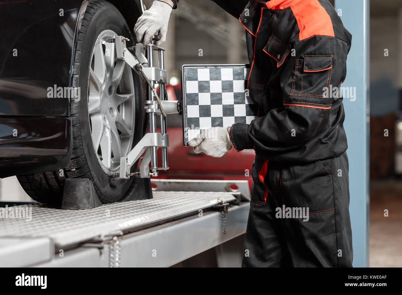 auto mechanic sets the car for diagnostics and configuration. Wheel alignment equipment on a car wheel in a repair - Stock Image