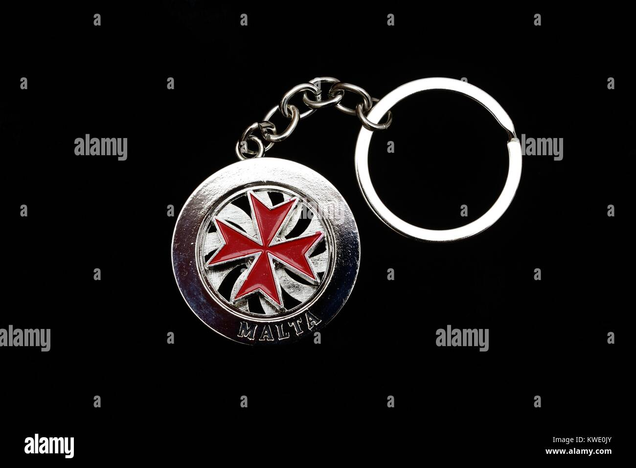 Circular Maltese key ring with a red cross in the centre which rotates against a black background - Stock Image
