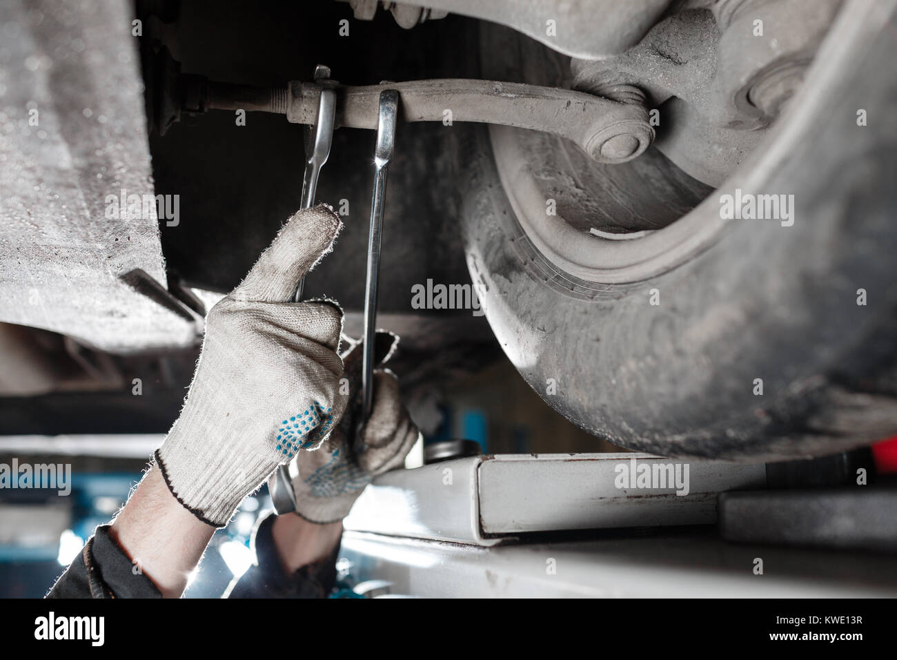 car mechanic examining car suspension of lifted automobile at repair service station - Stock Image