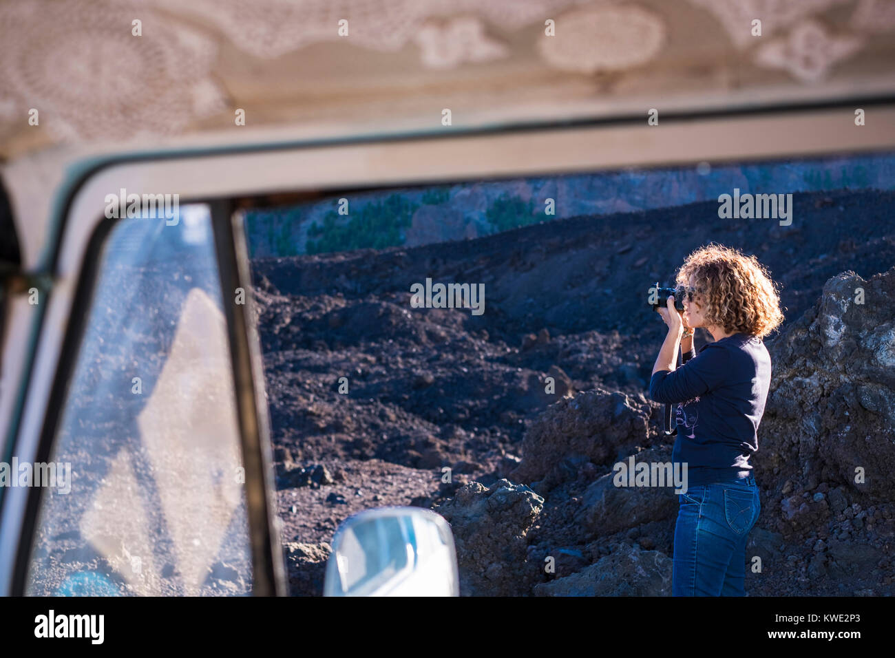 Woman photographing with camera seen through travel trailer's window - Stock Image