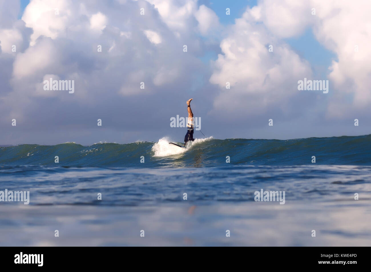 Low section of surfer doing stunts on surfboard against cloudy sky - Stock Image