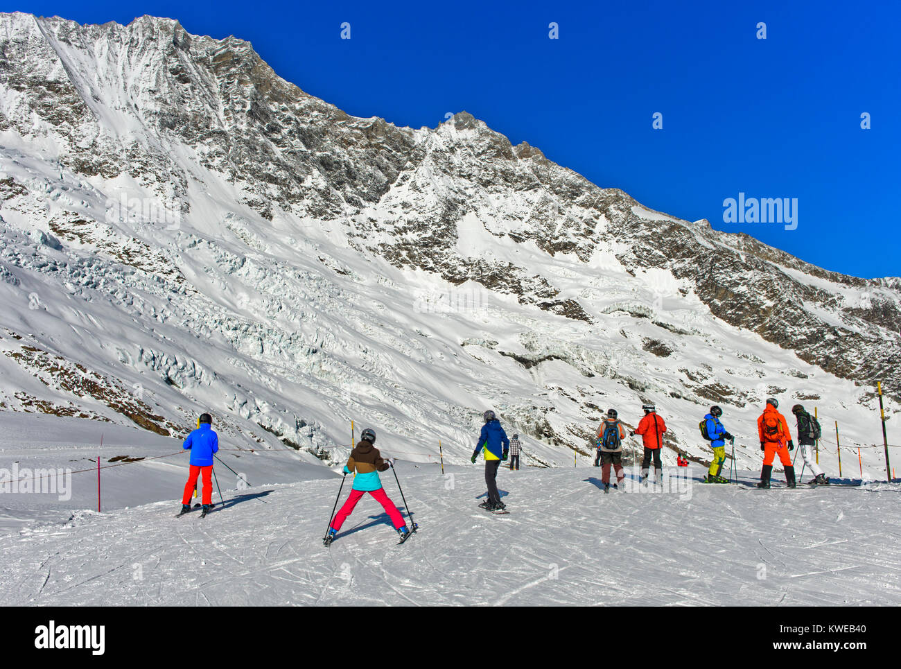 Skiers on the way to the Längfluh ski-run, Fee Glacier and the Mischabel massif behind, skiing area Saas-Fee, - Stock Image