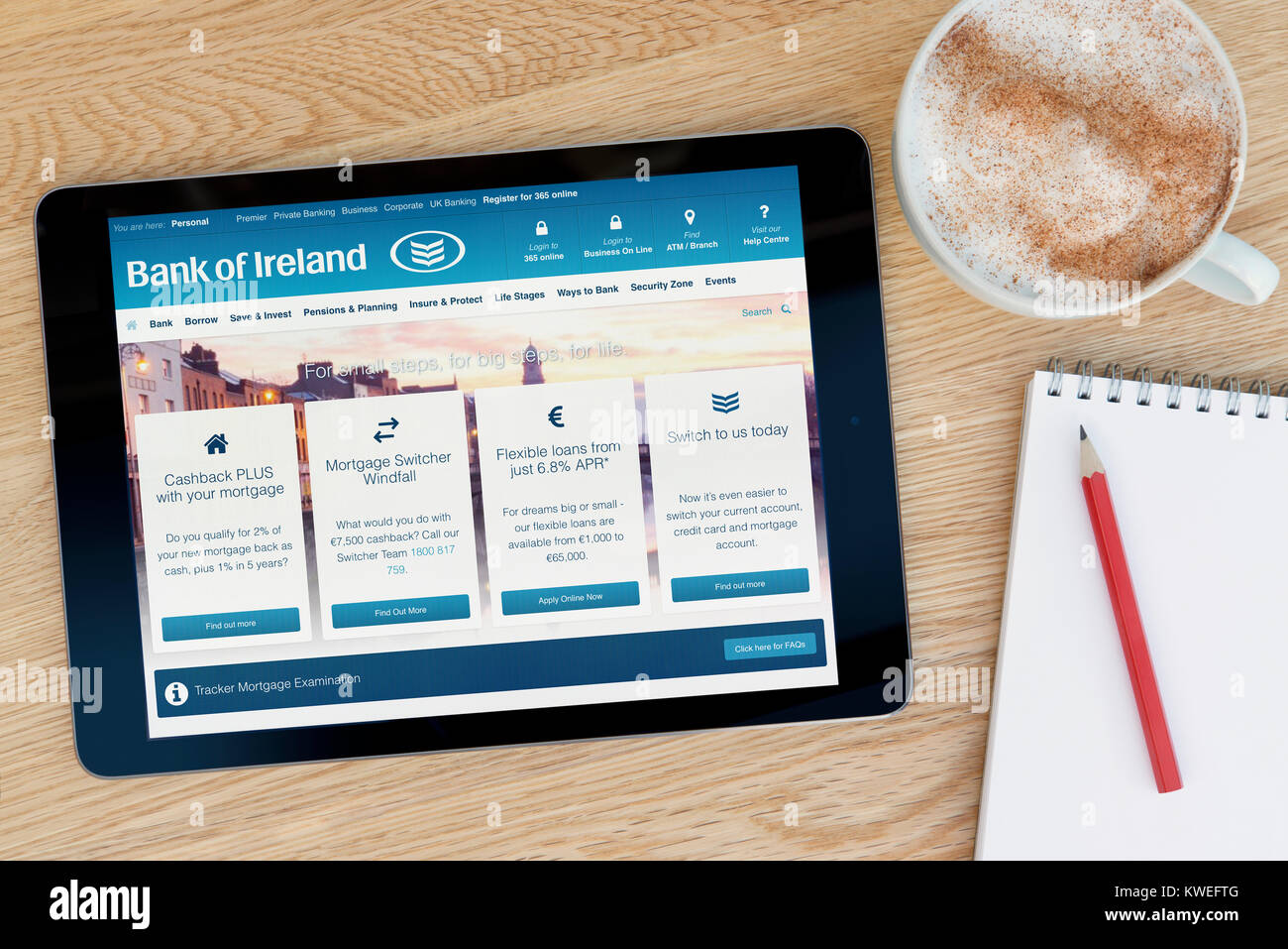 The Bank of Ireland website on an iPad tablet device, resting on a wooden table beside a notepad, pencil and cup - Stock Image