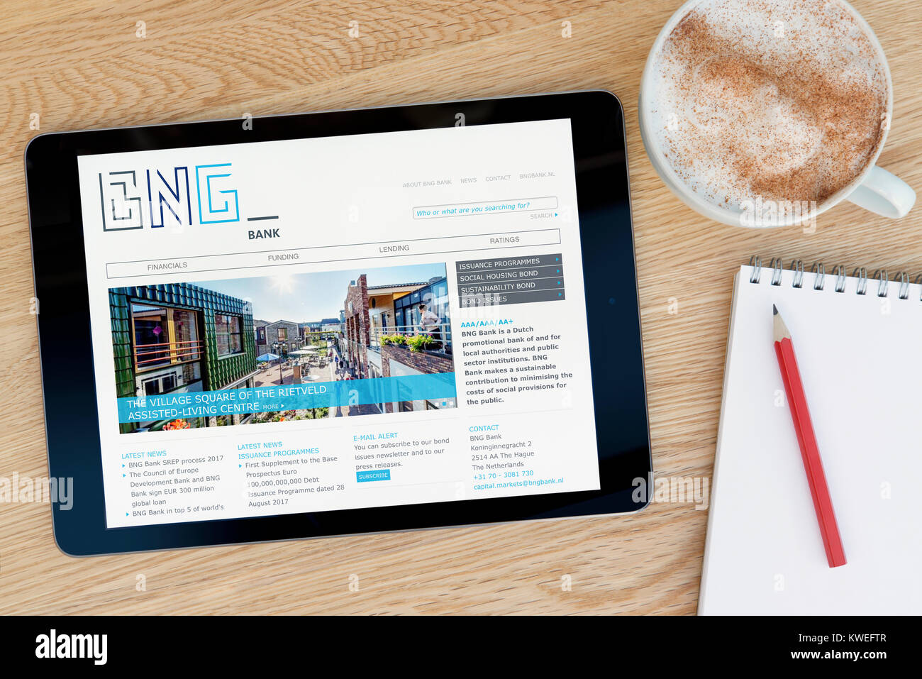 The BNG Bank website on an iPad tablet device, resting on a wooden table beside a notepad, pencil and cup of coffee - Stock Image
