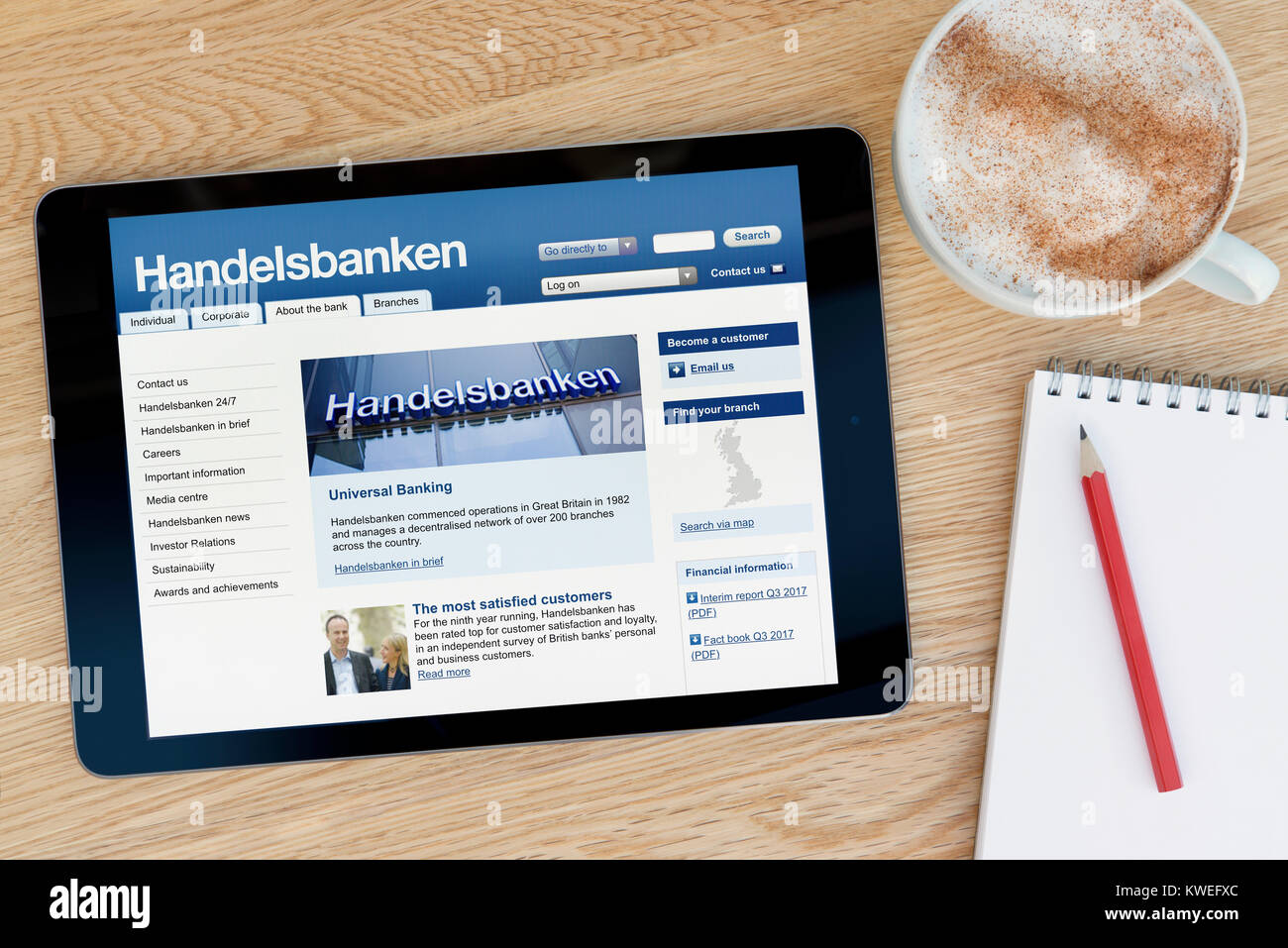 The Handelsbanken website on an iPad tablet device, resting on a wooden table beside a notepad, pencil and cup of - Stock Image