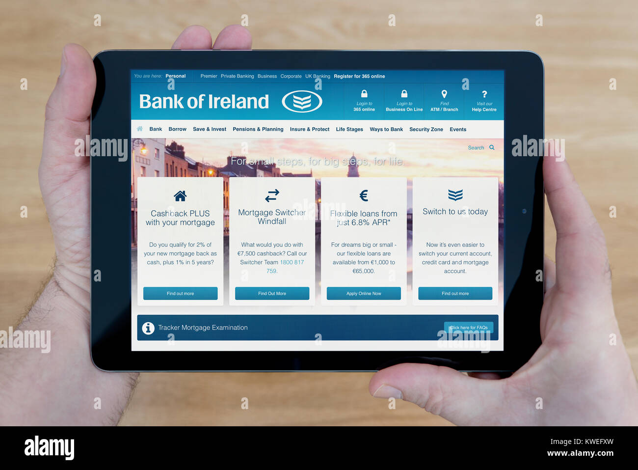 A man looks at the Bank of Ireland website on his iPad tablet device, shot against a wooden table top background - Stock Image