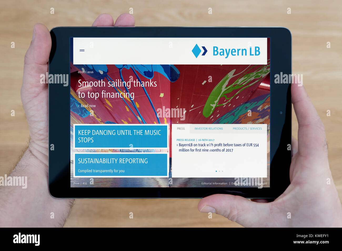 A man looks at the BayernLB (Bayerische Landesbank) bank website on his iPad tablet device, over wooden table top - Stock Image