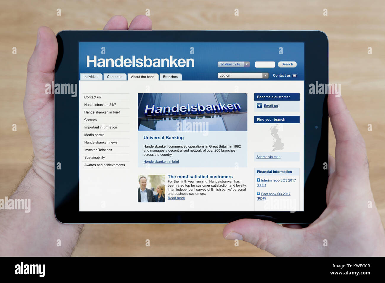 A man looks at the Svenska Handelsbanken website on his iPad tablet device, shot against a wooden table top background - Stock Image