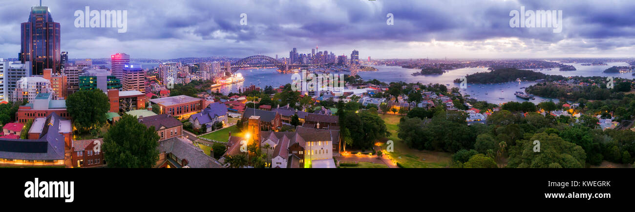 Panorama of SYdney city CBD from North Sydney office towers and high-rises at sunset across blurred blue sydney - Stock Image