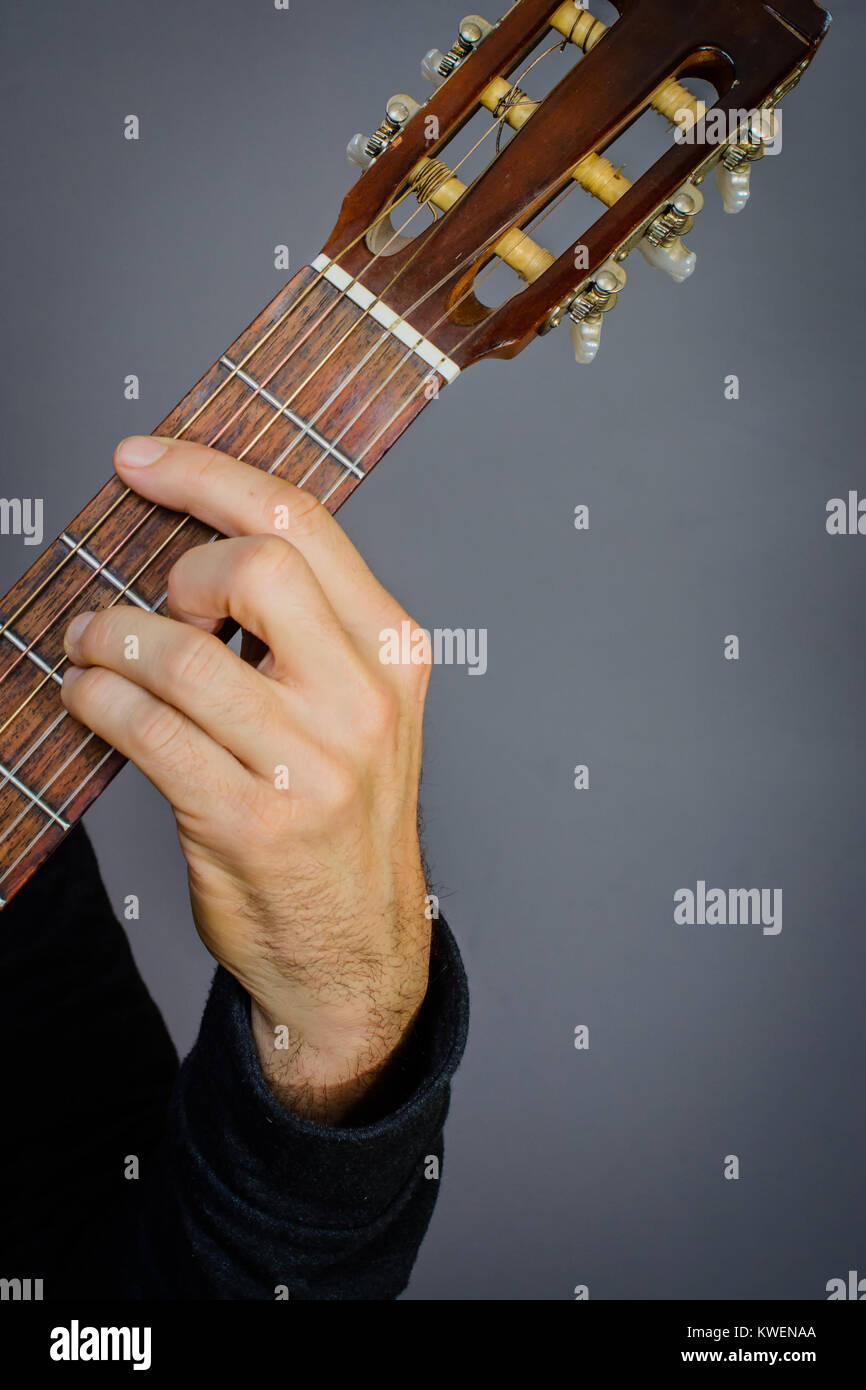 Guitarist Playing An B Minor Chord On Classical Acoustic Guitar With