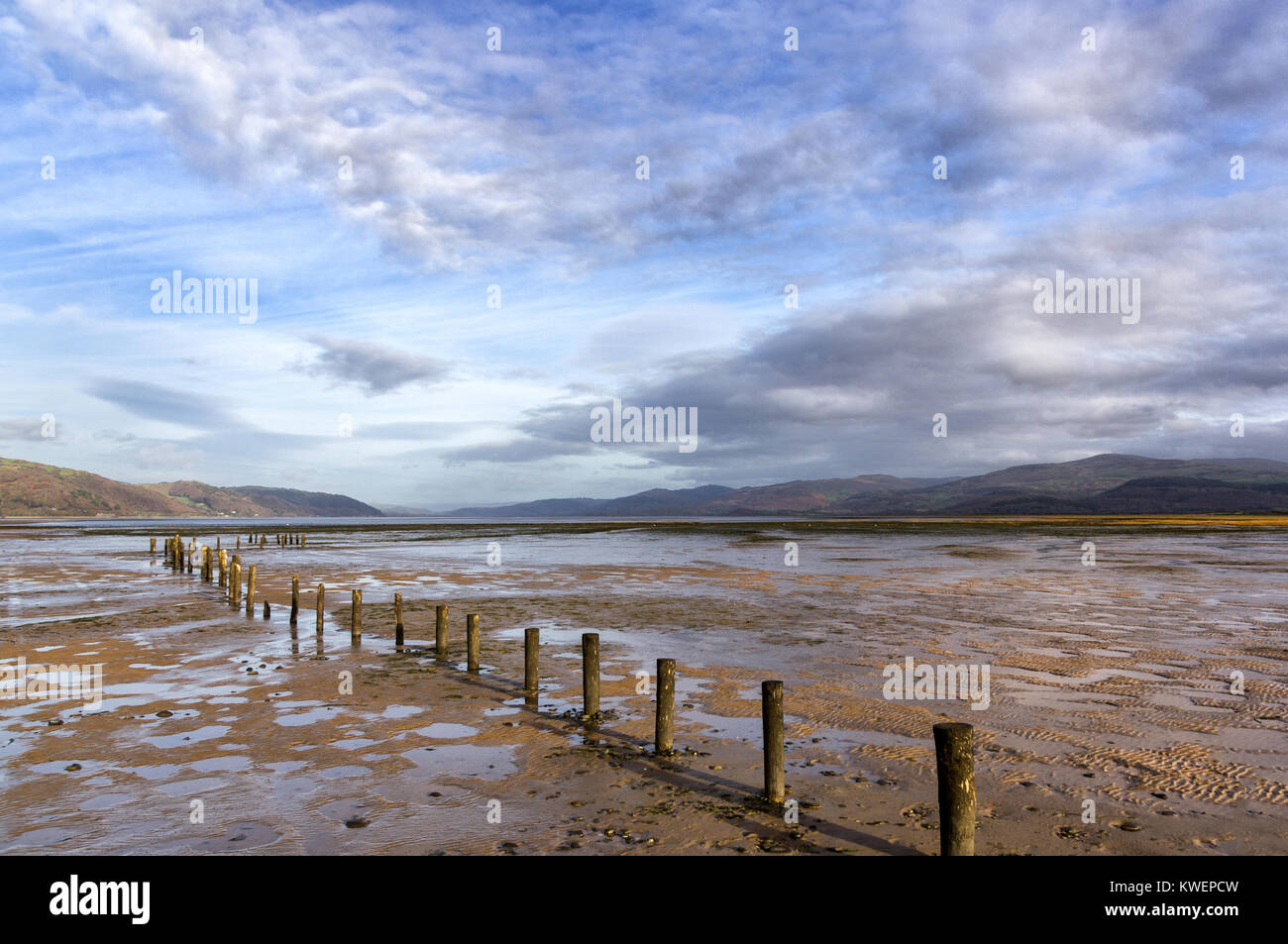 Sunny autumn light at Ynyslas nature reserve, Dovey Estuary, Wales at low tide, eroded fence in foreground and Cambrian Stock Photo