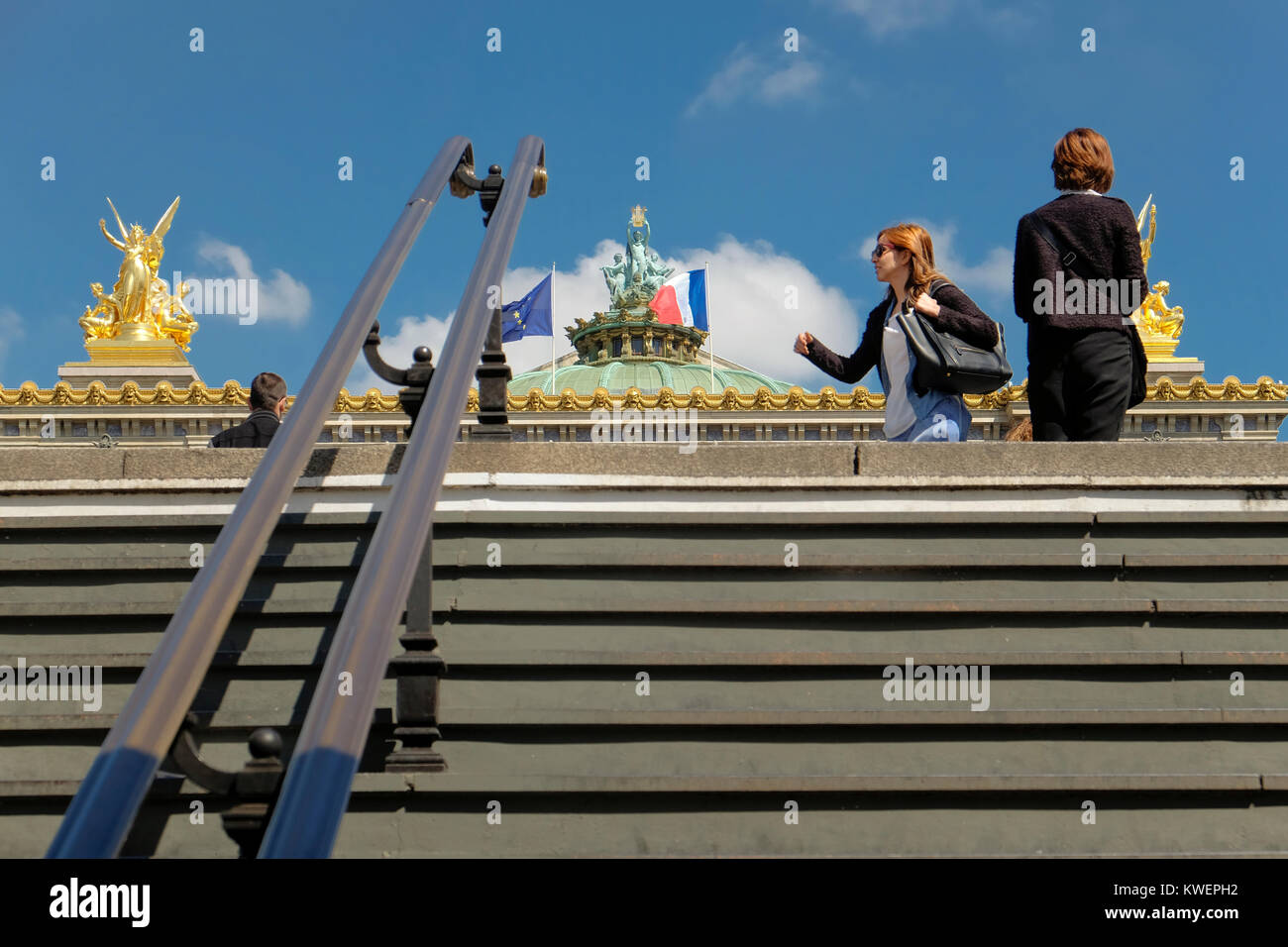 France, Paris, Two women with roof of Opera Garnier behind them. - Stock Image