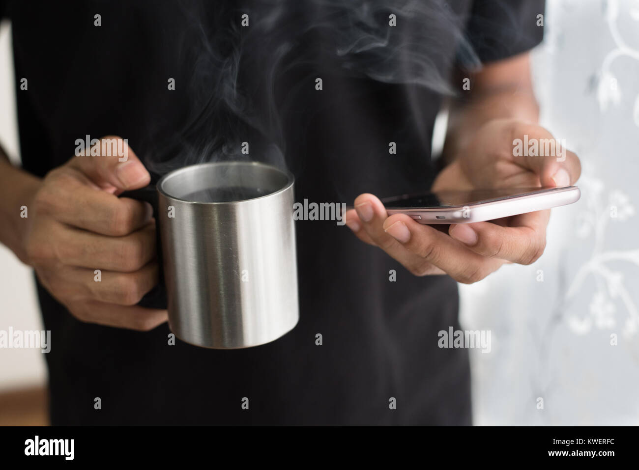 man holding a cup of coffee while using smartphone in his home. weekend lifestyle concept - Stock Image