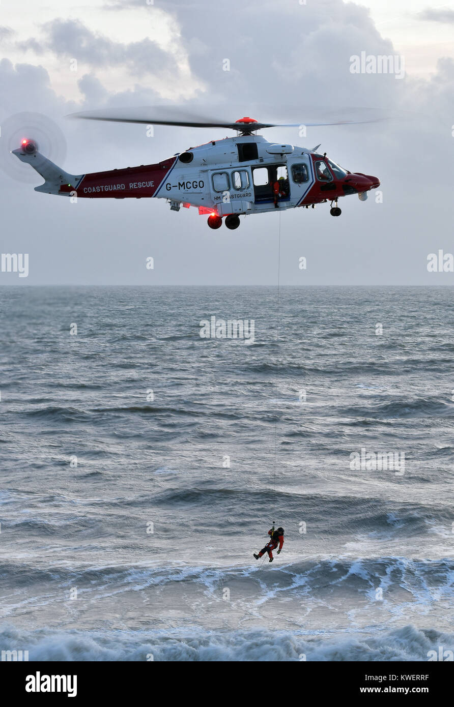 The coastguard search and rescue helicopter hovering over a rough and stormy sea at St Catherines point on the Isle - Stock Image