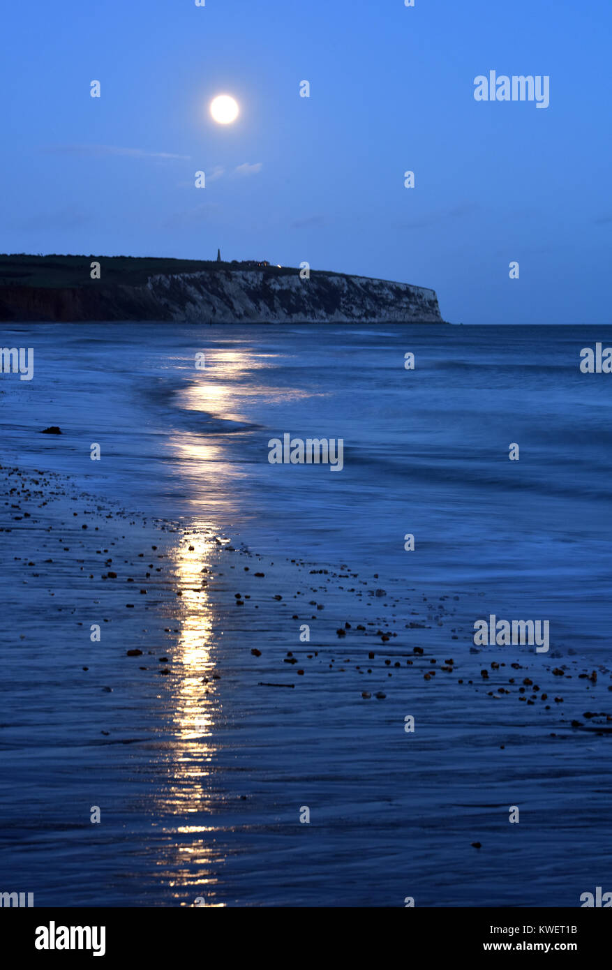 A super moon rising over the downs at Culver on the Isle of Wight with Sandown bay beach and waves in the foreground. Stock Photo