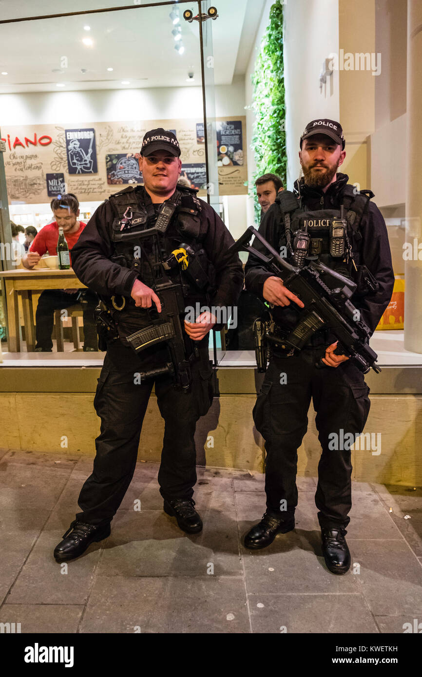 Heavily armed policemen on duty at Edinburgh Hogmanay street party on New Year's Eve in Scotland , United Kingdom - Stock Image