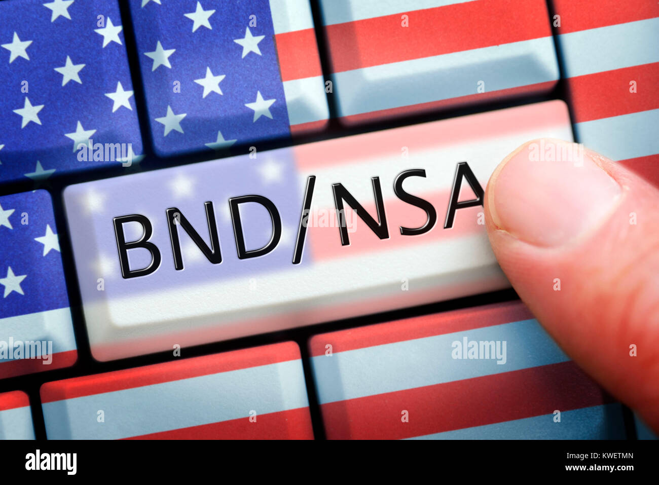 Finger on computer key with NSA and Federal Intelligence Service stroke on USA-national colours, symbolic photo - Stock Image