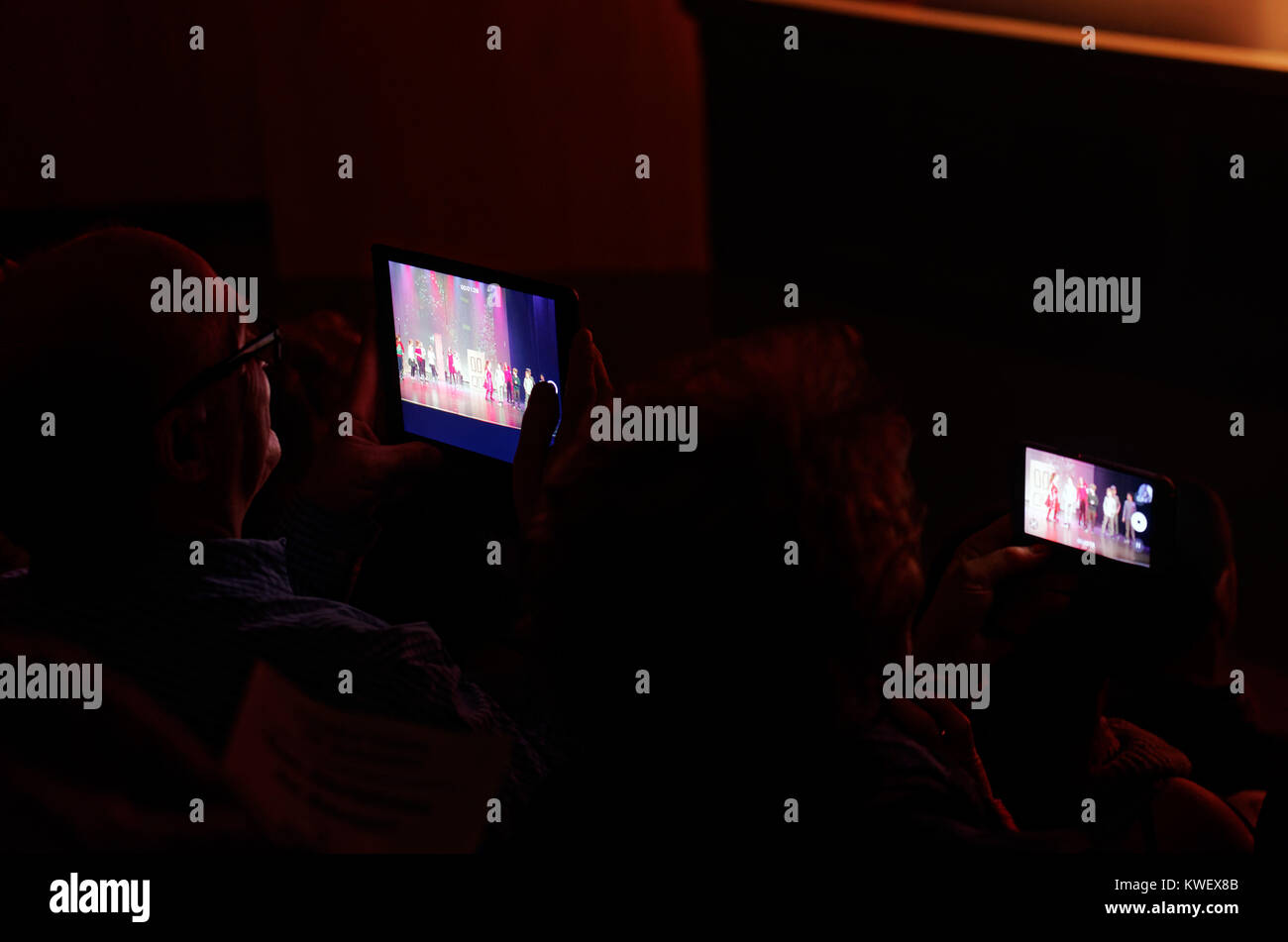 Grandparents filming a children's christmas show on their ipad and iphone - Stock Image