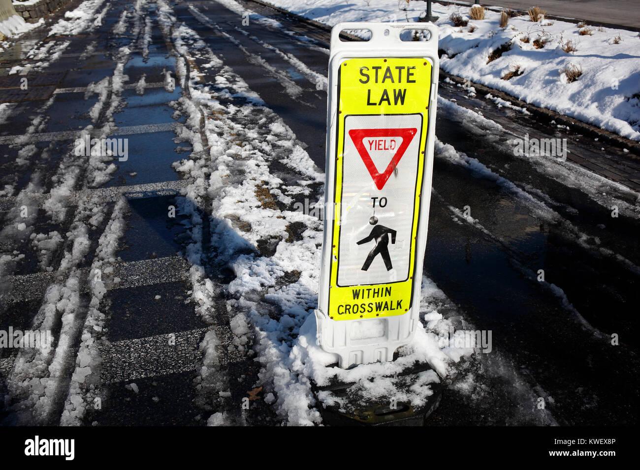 Yield to pedestrians in crosswalk sign on slushy bike lane in Hudson River Park, New York City - Stock Image