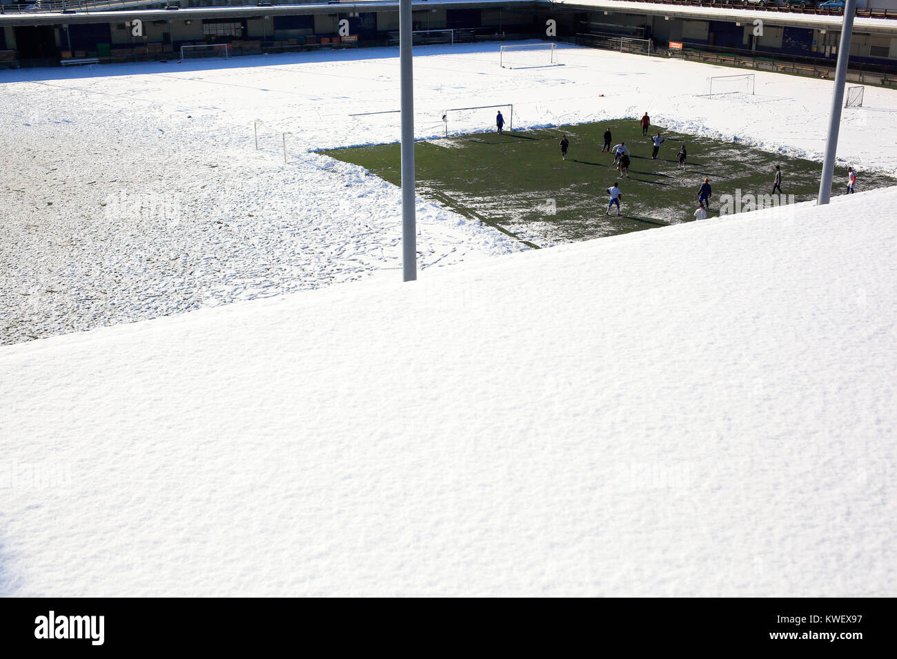 Soccer match in winter on snow plowed sport field . - Stock Image