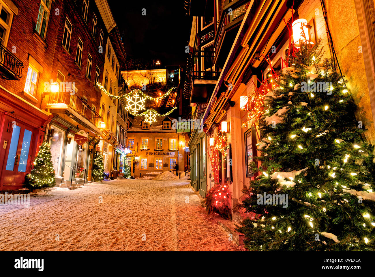 Christmas decorations and fresh snow in Quebec City's Petit Champlain area at night. Looking up Rue Sou-le-Fort - Stock Image