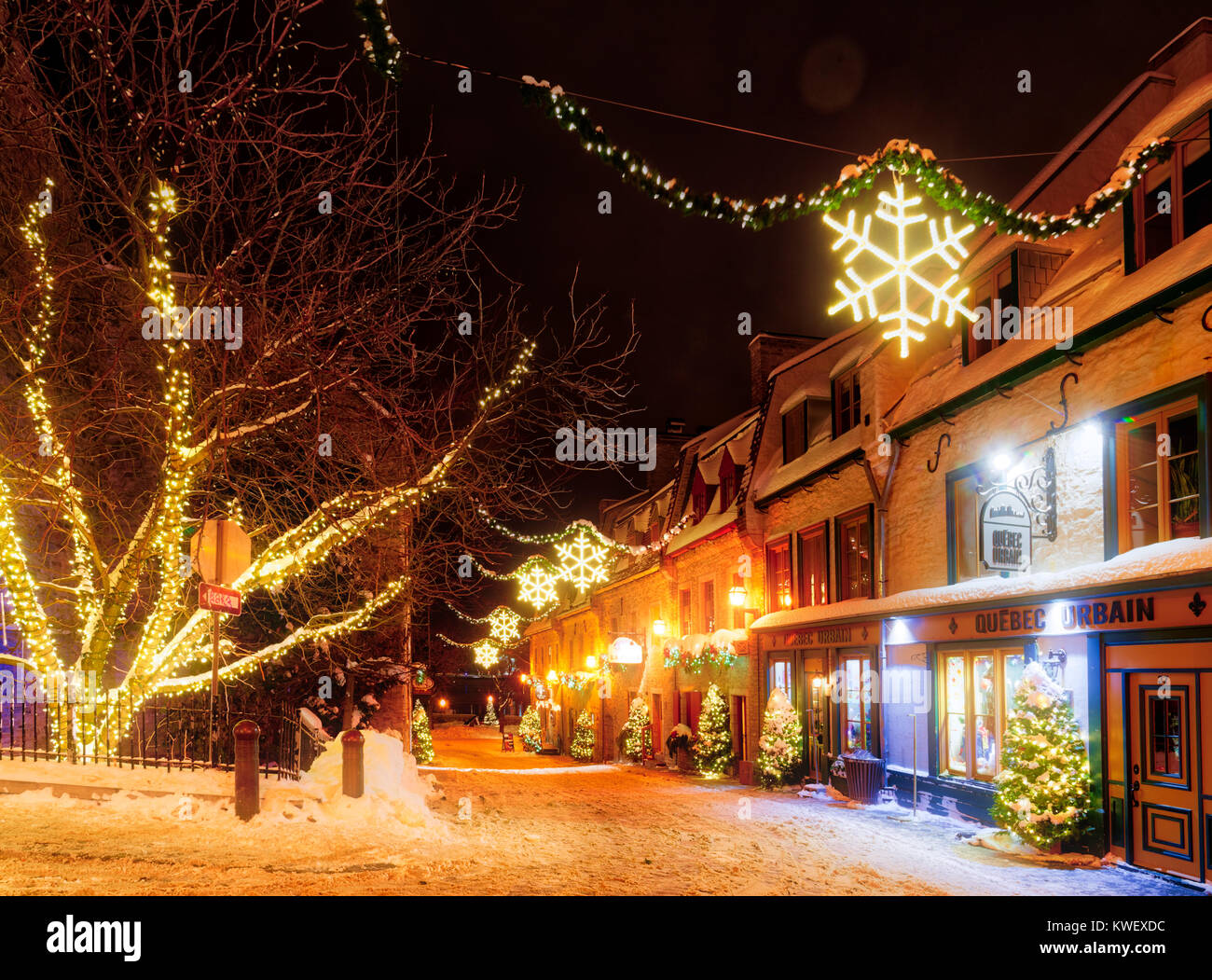 Christmas decorations and fresh snow in Quebec City's Petit Champlain area at night- looking along Rue St Pierre - Stock Image